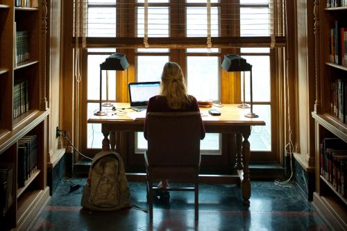 woman sitting at desk in front of window with back to camera, light streaming through, surrounded by books, working on a laptop