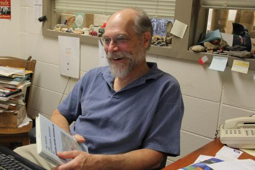 bearded man with glasses (dennis trombatore) smiling at desk with book in hands
